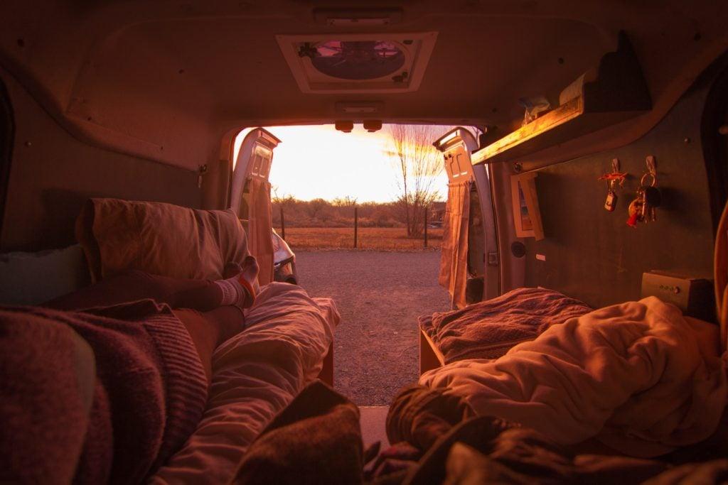 Van life is helping Sarah pay off her debt. Click here to learn more about living in a van and how she built her van dwelling. #vanlife #vandwelling #vanlifehacks #vanlifeDIY #vanlifeideas